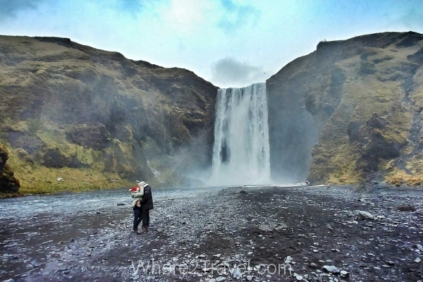 Couple kissing in front of Skogafoss waterfall